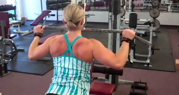 Вертикальная тяга в тренажере. Техника выполнения сидя, на спину, за голову, узким хватом для женщин